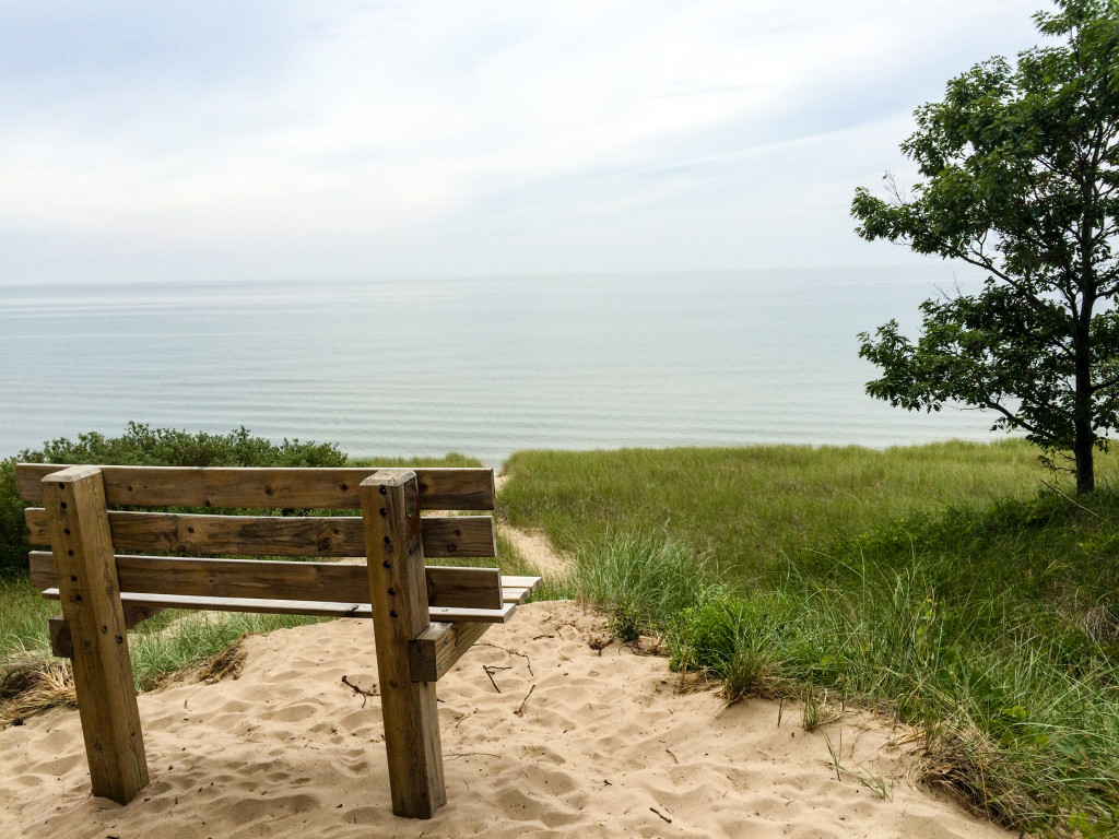 A bench atop a sand dune overlooks the Lake Michigan beach at Saugatuck Dunes State Park in Saugatuck, Michigan.