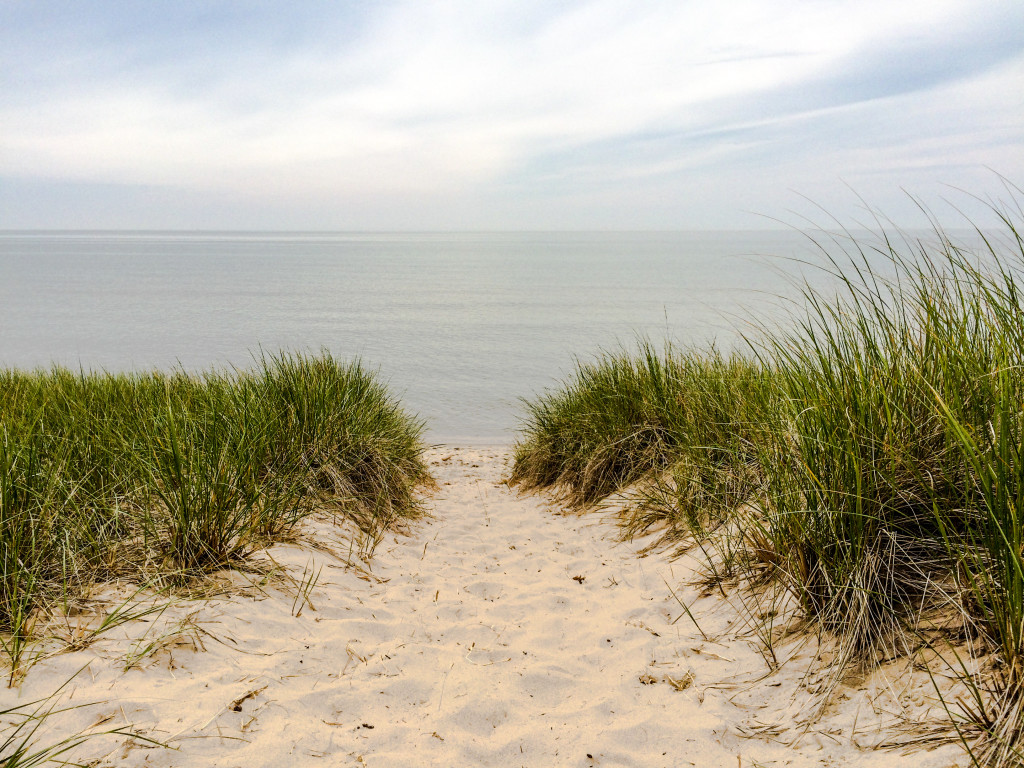 A small sand dune leads to Lake Michigan at Saugatuck Dunes State Park in Saugatuck, Michigan