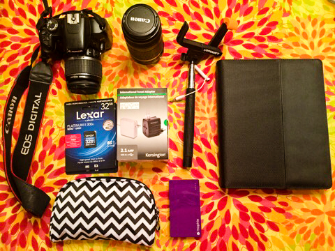 Technology packed for Peru: Canon Rebel, telephoto lens, selfie stick, iPad with keyboard folio, Mophie chargers, adapter, memory cards, and chargers packed in cosmetic case.