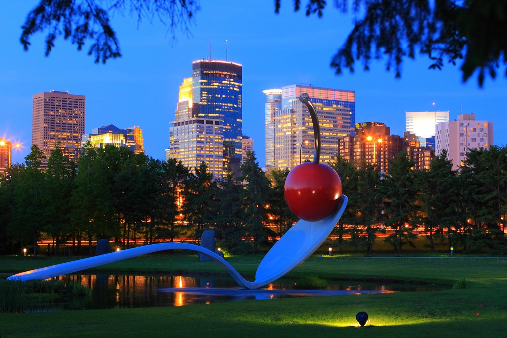 "The Minneapolis skyline shines behind the Spoonbridge and Cherry at the Minneapolis Sculpture Garden, part of the Walker Art Center collection. (Photo courtesy of Meet Minneapolis | Spoonbridge and Cherry, Claes Oldenburg and Coosje van Bruggen, 1985-1988, aluminum, stainless steel, paint, 354 x 618 x 162""overall, Collection Walker Art Center, Minneapolis, Gift of Frederick R. Weisman in honor of his parents, William and Mary Weisman, 1988, Art © Claes Oldenburg and Coosje van Bruggen)"
