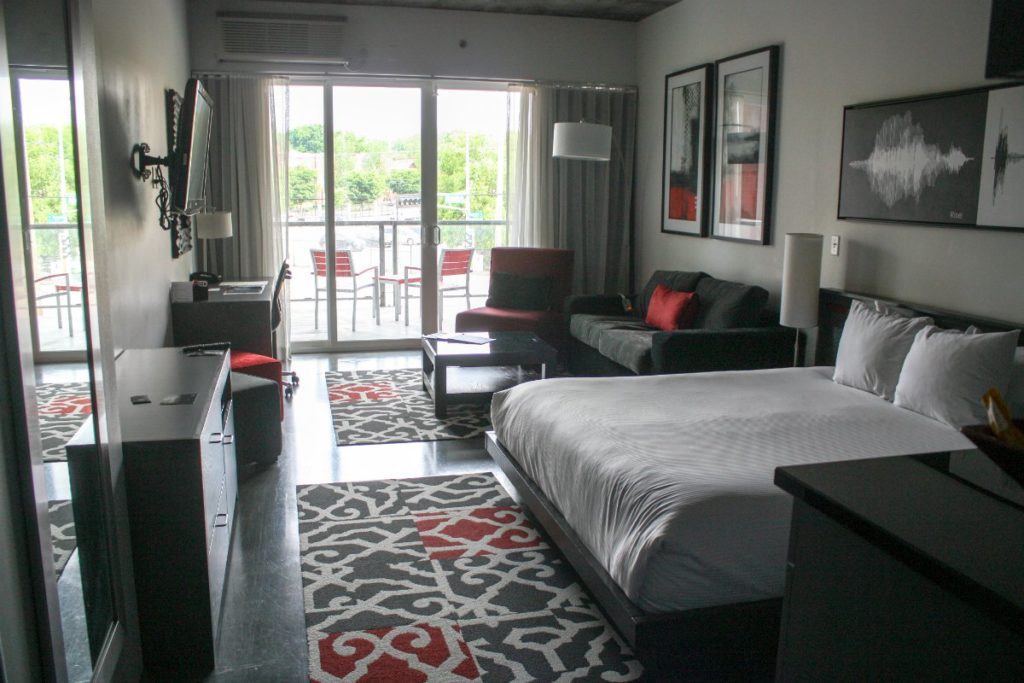 This HotelRED room is outfitted with a king bed, living area, kitchenette, flat-screen TV, desk, and balcony. (Erin Klema/The Epicurean Traveler)