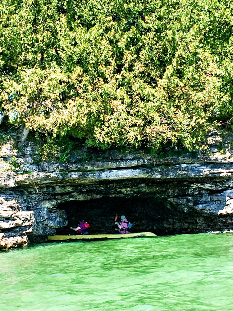 Kayakers paddle into a cave with Door County Kayak Tours. (Erin Klema/The Epicurean Traveler)