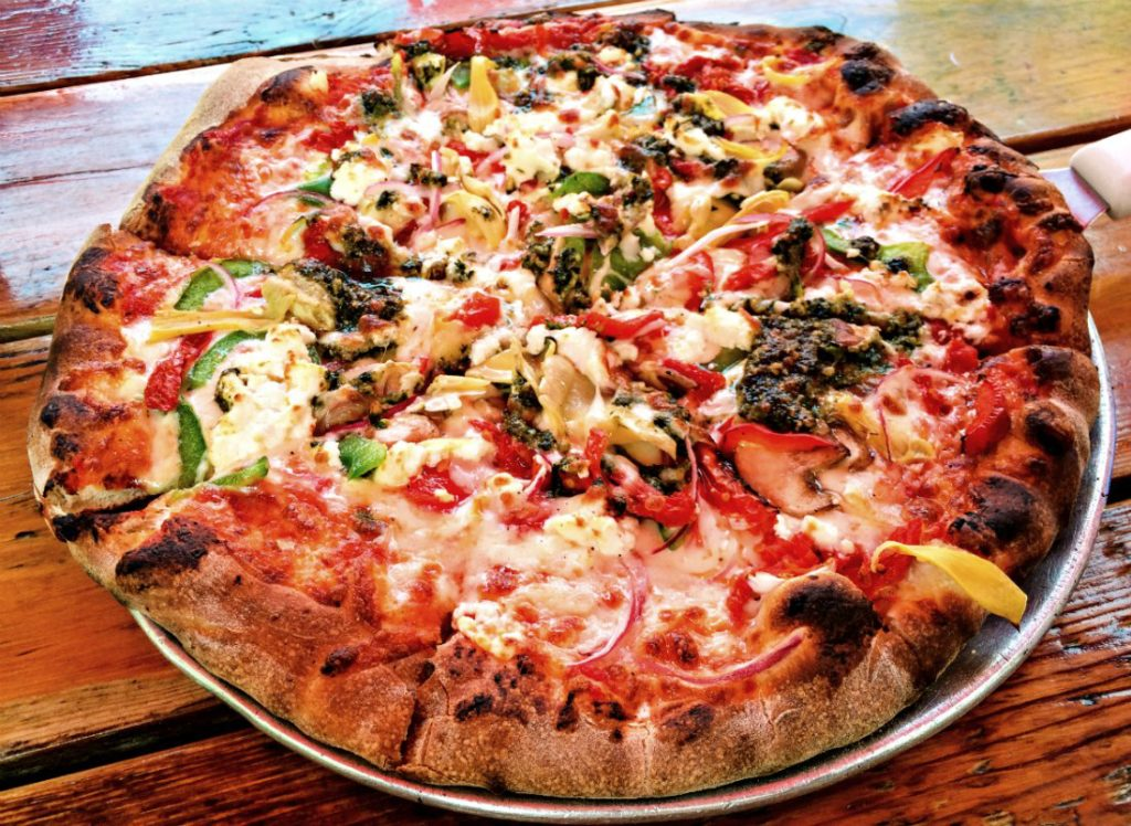The veggie pizza is topped with red and green bell peppers, onions, mushrooms, artichoke hearts, sun dried tomatoes, pesto, Wisconsin goat cheese, and mozzarella at Wild Tomato in Fish Creek. (Erin Klema/The Epicurean Traveler)