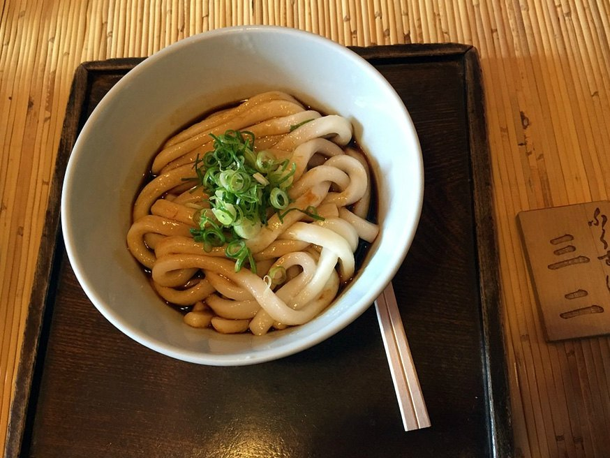 Udon, a Japanese specialty rice noodle with umami soupbase and scallion.