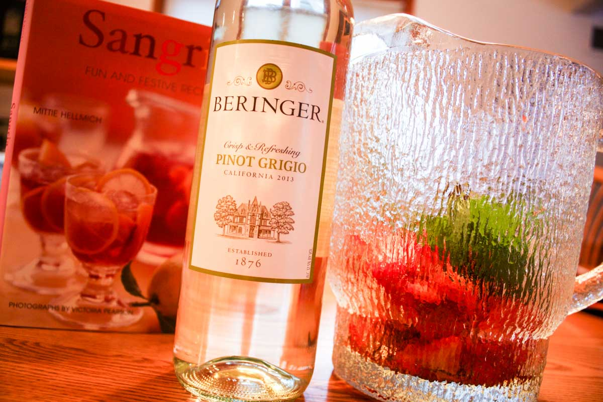 Sangria cookbook with Beringer Pinto Grigio bottle and glass pitcher filled with mint and strawberries