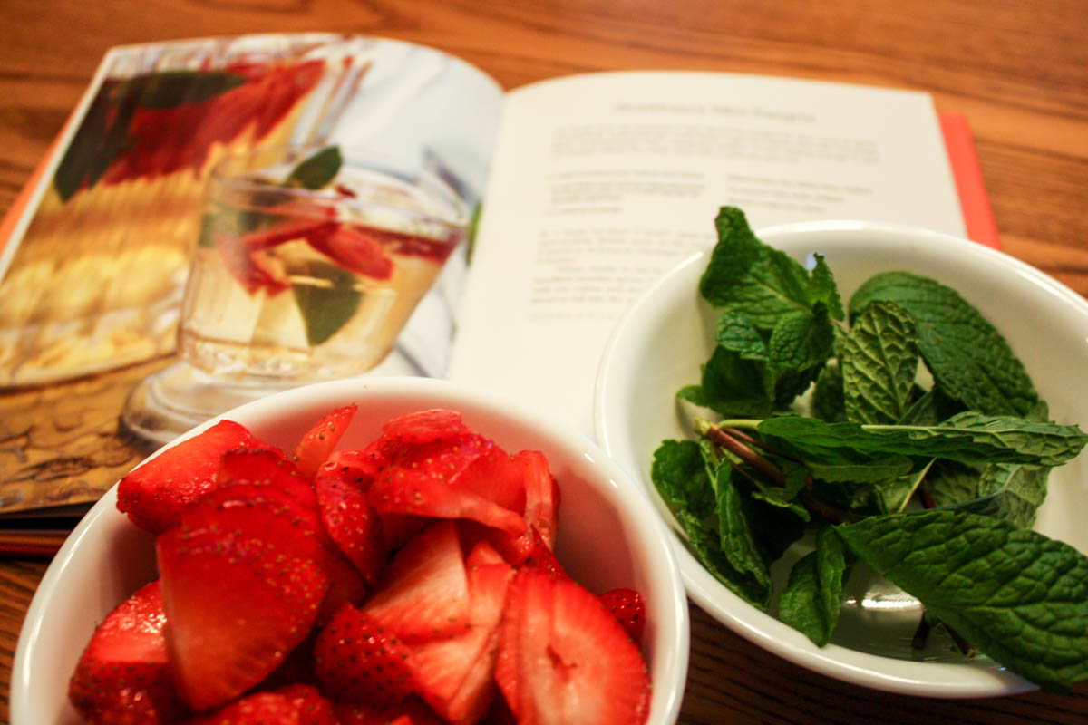 Strawberry Mint White Sangria recipe opened in cookbook with bowls sliced strawberries and mint leaves