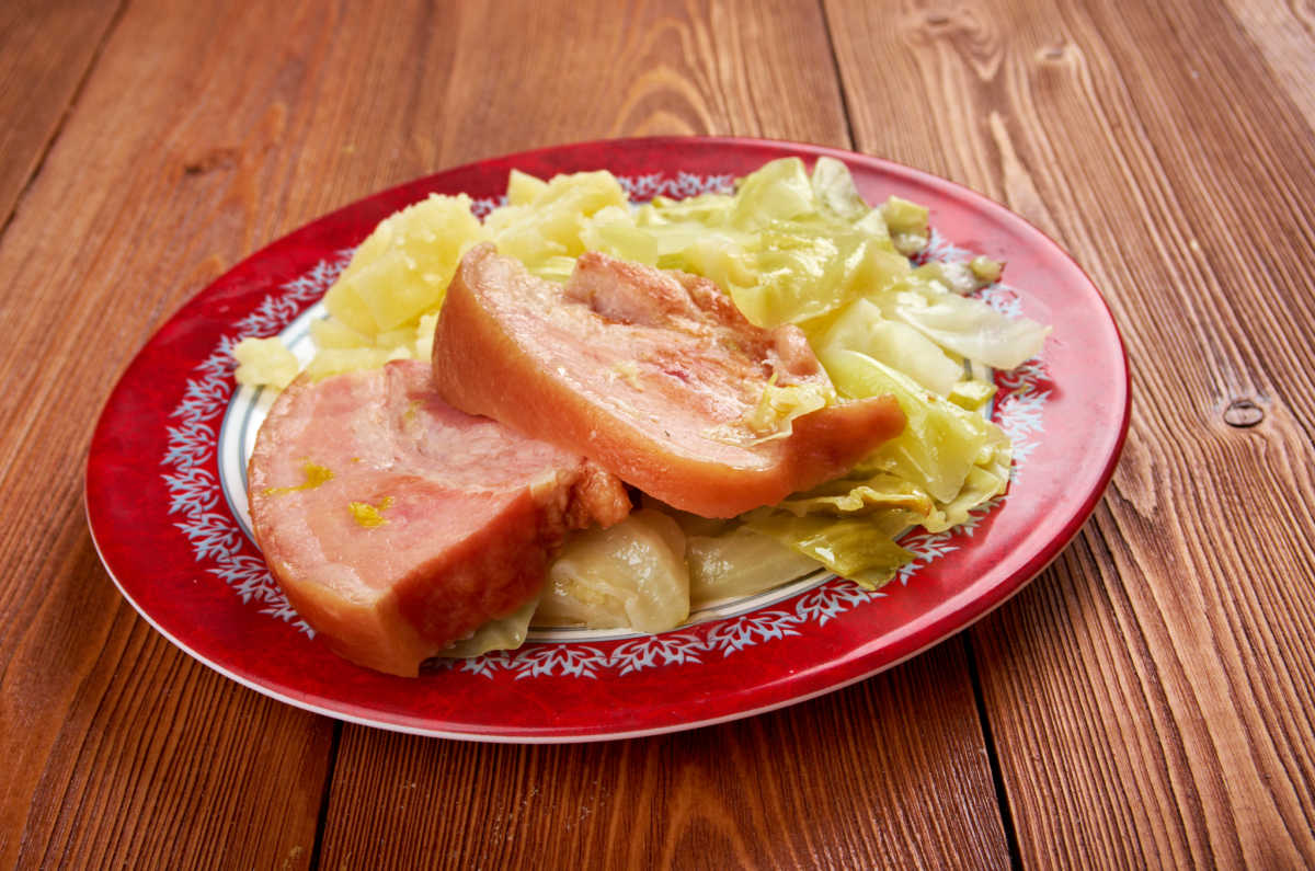Irish bacon and cabbage dish on red plate
