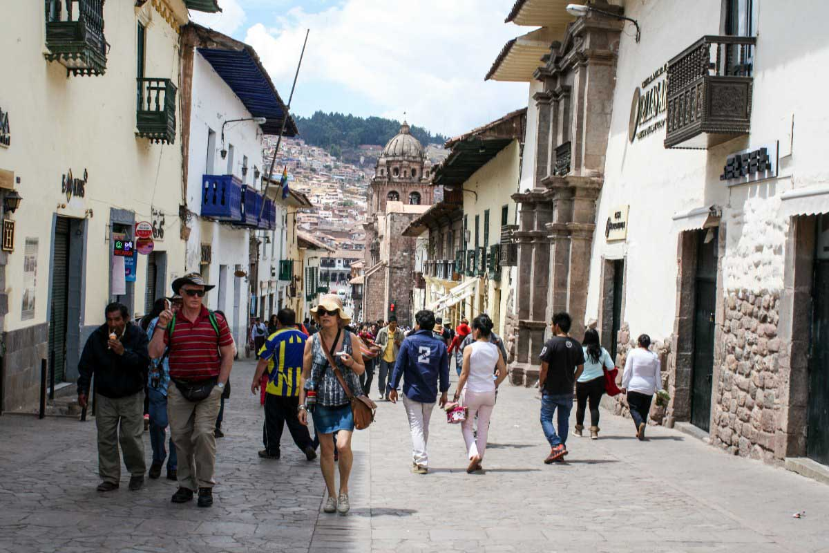 Travelers and locals walk down a street in Cusco, Peru.