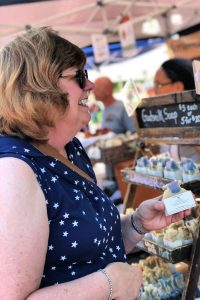 Shopper buying goat's milk soap at Bloomington Community Farmers' Market