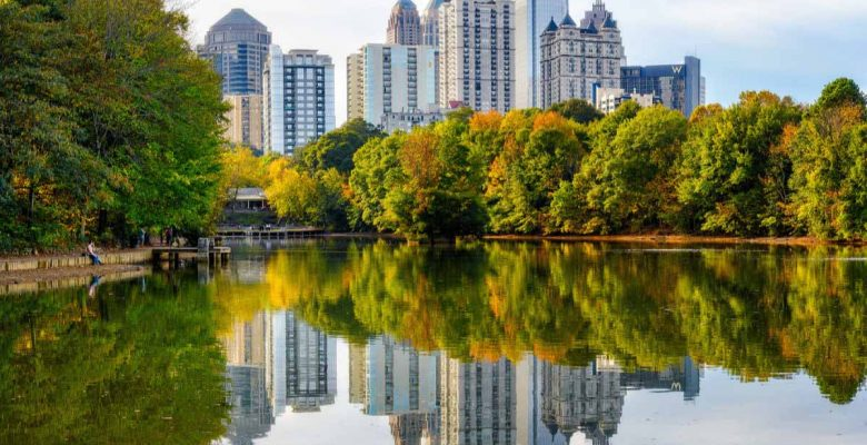 The Atlanta Midtown skyline is reflected in Lake Clara Meer at Piedomont Park.