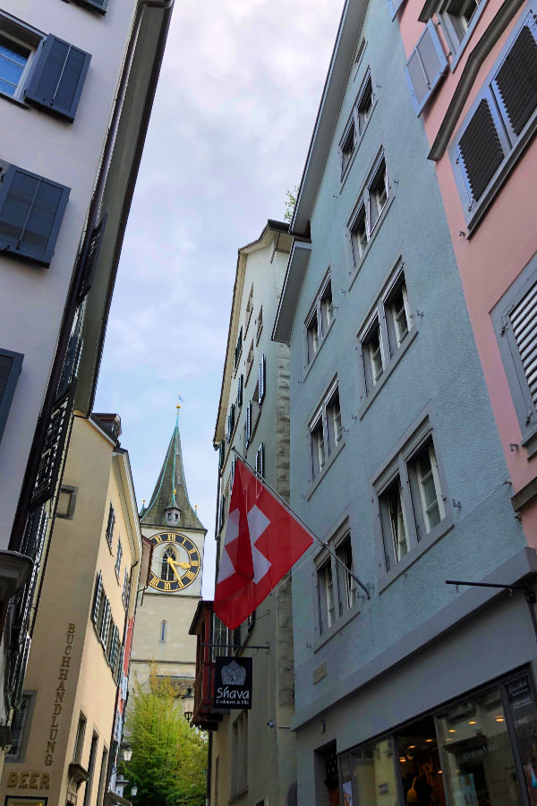 The Church of St. Peter's clock peeking through alleyway of colorful buildings displaying Swiss flag