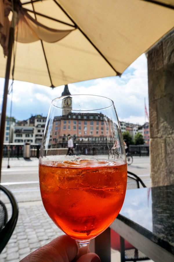 Hand holding Aperol Spritz under tan umbrella with view of Zurich, Switzerland