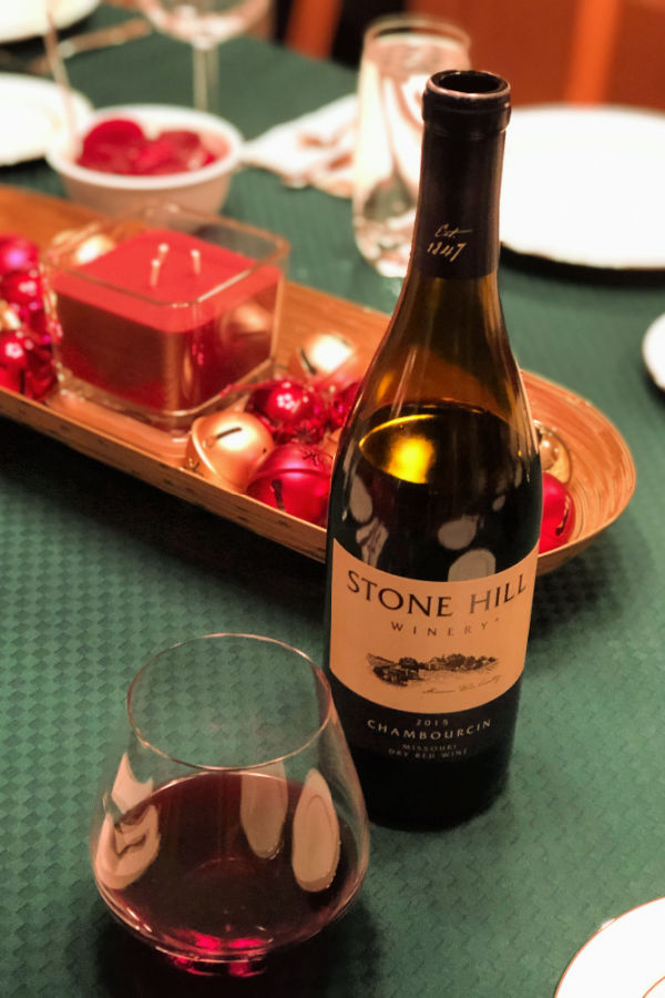 Stone Hill Winery 2015 Chambourcin in bottle and stemless wine glass on green cloth-covered table decorated for Christmas