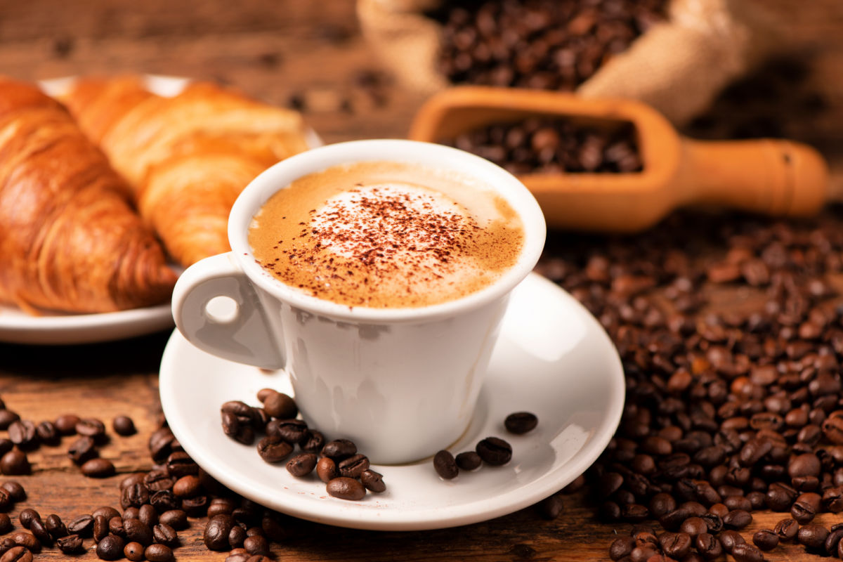 A cup of cappuccino with coffee bean as background close up