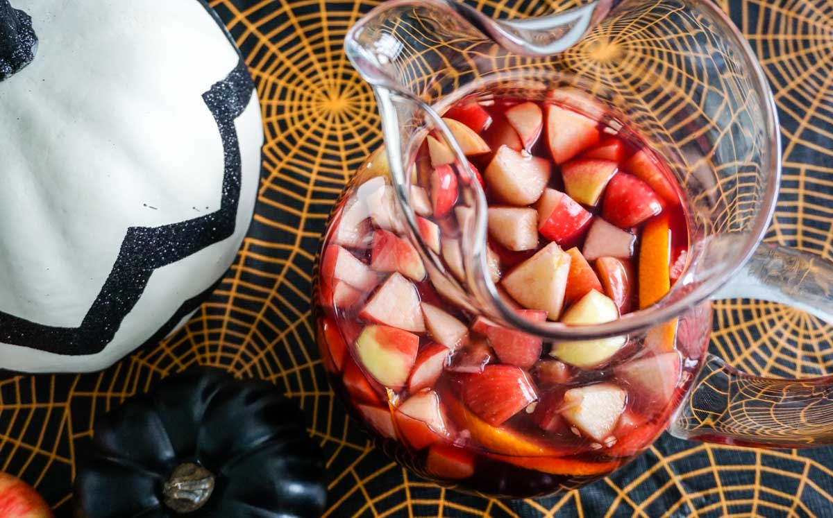 Overhead shot of Michigan Apple Cider Sangria in glass potbelly pitcher in Halloween table setting