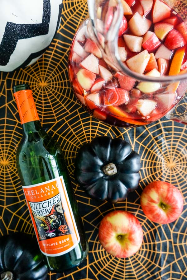 Leelanau Cellars Witches Brew wine bottle with Honeycrisp apples and sangria in Halloween setting