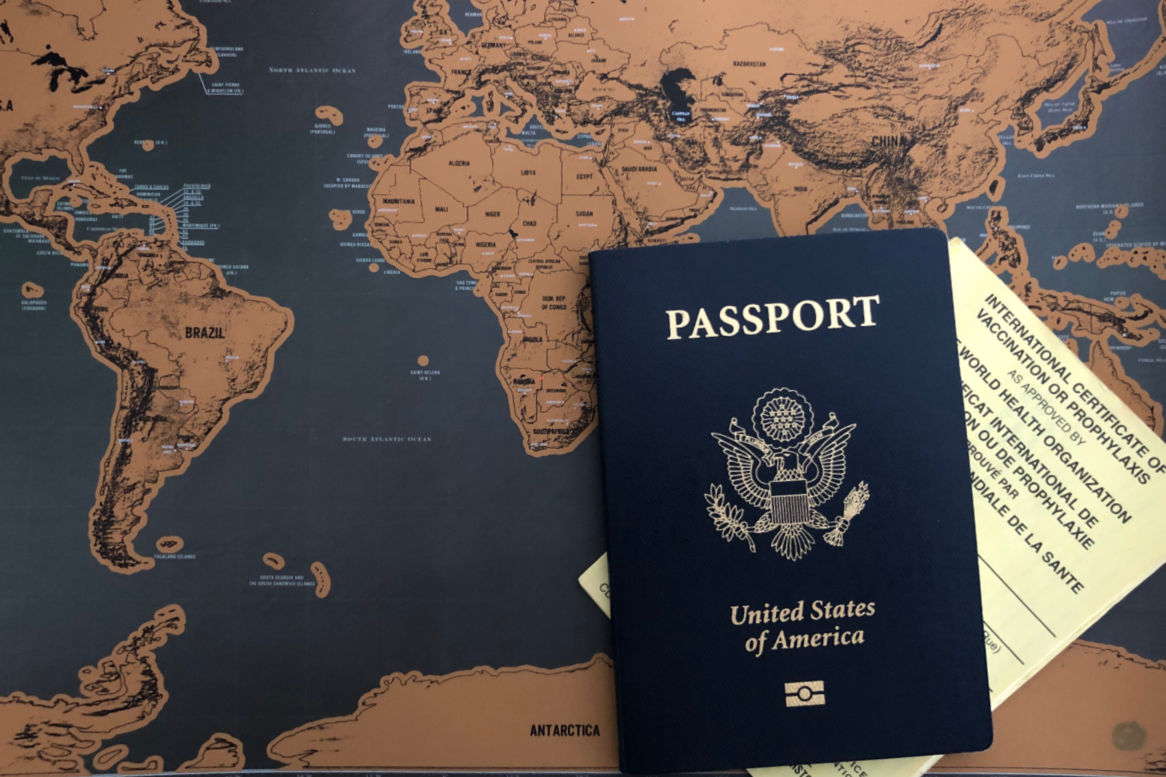United States passport with vaccination certificate and world map background