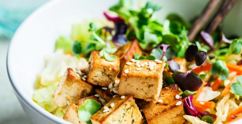 Fried tofu salad with sprouts and sesame seeds in a white bowl